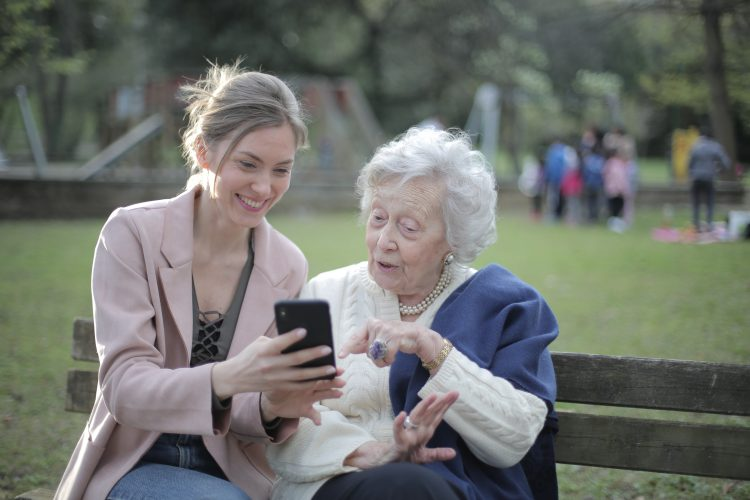 cheerful-senior-mother-and-adult-daughter-using-smartphone-3791664