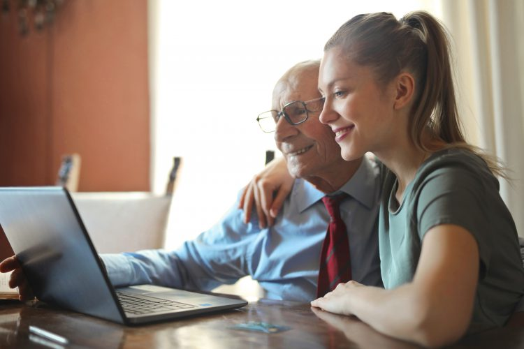 young-positive-woman-helping-senior-man-using-laptop-3823489
